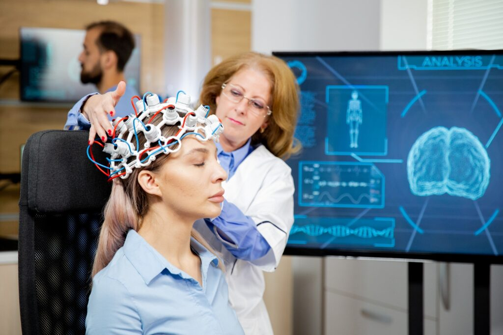 Doctor arranging neurology scanning headset for tests on a female patient
